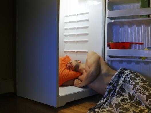 Man sleeping in his open fridge to cool off