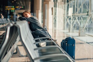 Person sleeping in the airport chairs, feeling the impact of jet lag