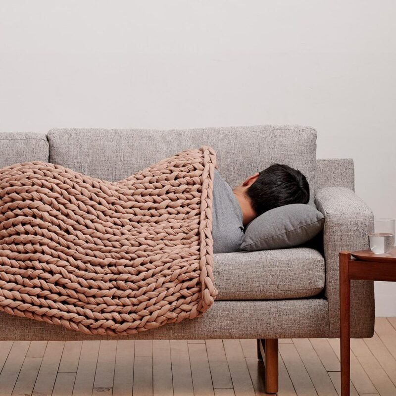 Man sleeping under a Bearaby weighted blanket