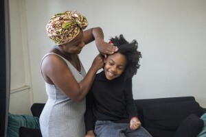 Black mother with a hair wrap combing her daughter's hair.