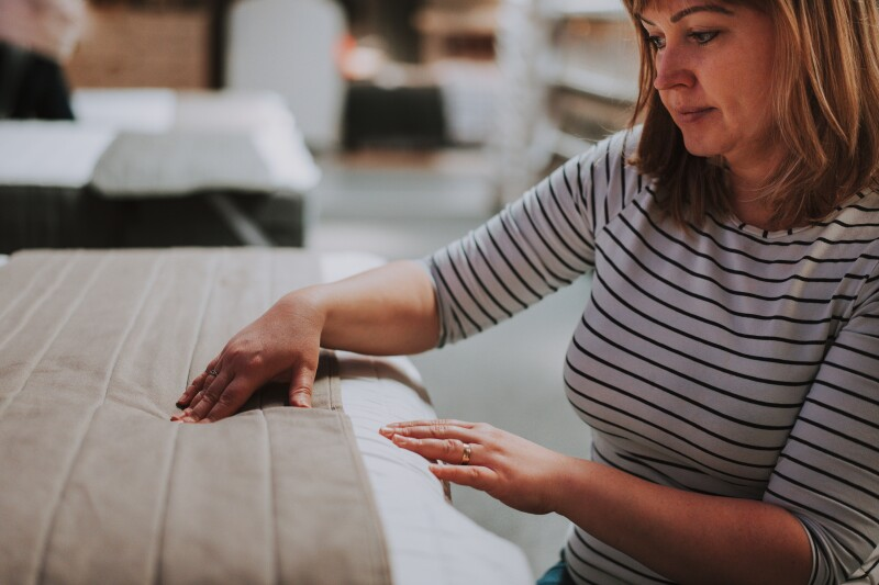 A woman choosing the right type of mattress protector.