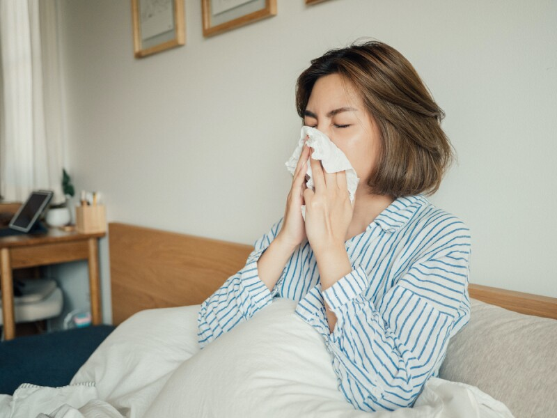 Woman waking up to allergies after a night of sleep