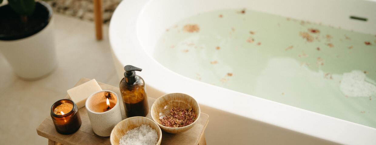 Bath tub with candles, bath salts, and dried flowers on a side table.