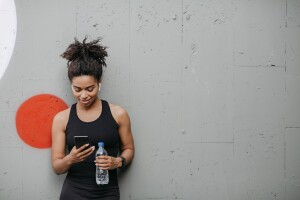 Black woman holding a plastic water bottle and looking at her phone after a workout