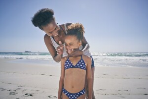 Parent applying sunscreen on tip of their child's nose while at the beach