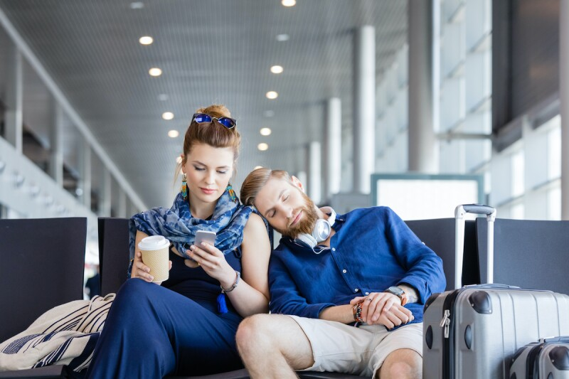 Traveling couple in an airport, waiting for their flight. One of them is sleeping on their partner, with their head on their shoulder