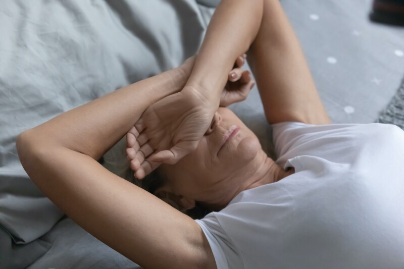 Woman covering eyes from sleep problems caused by menopause