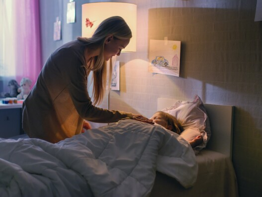 Parent sitting next to child in bed for support and relaxation to avoid night terrors during sleep.
