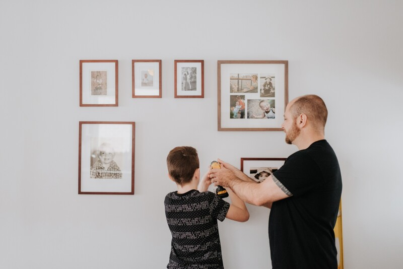 Father teaching son to put up family photos