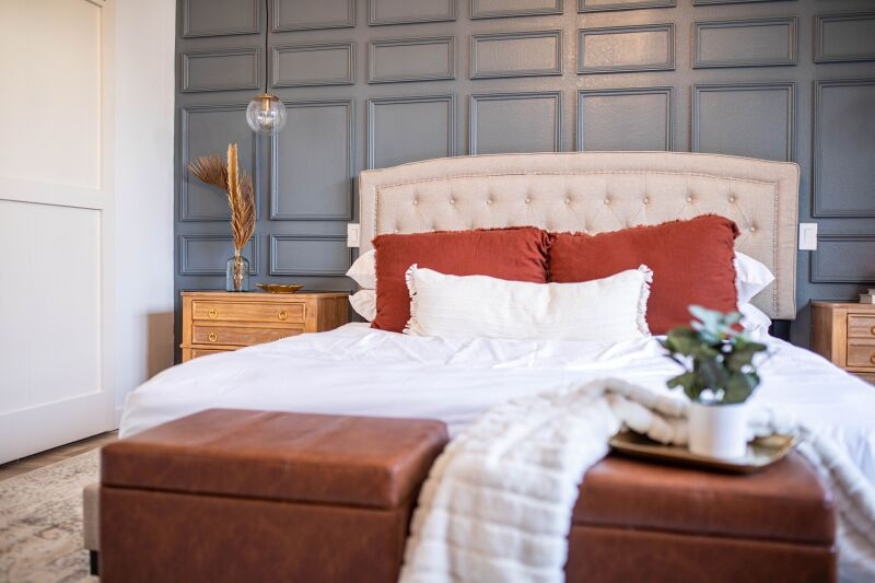 Medium shot of a bed covered in white sheets and burnt orange pillows.
