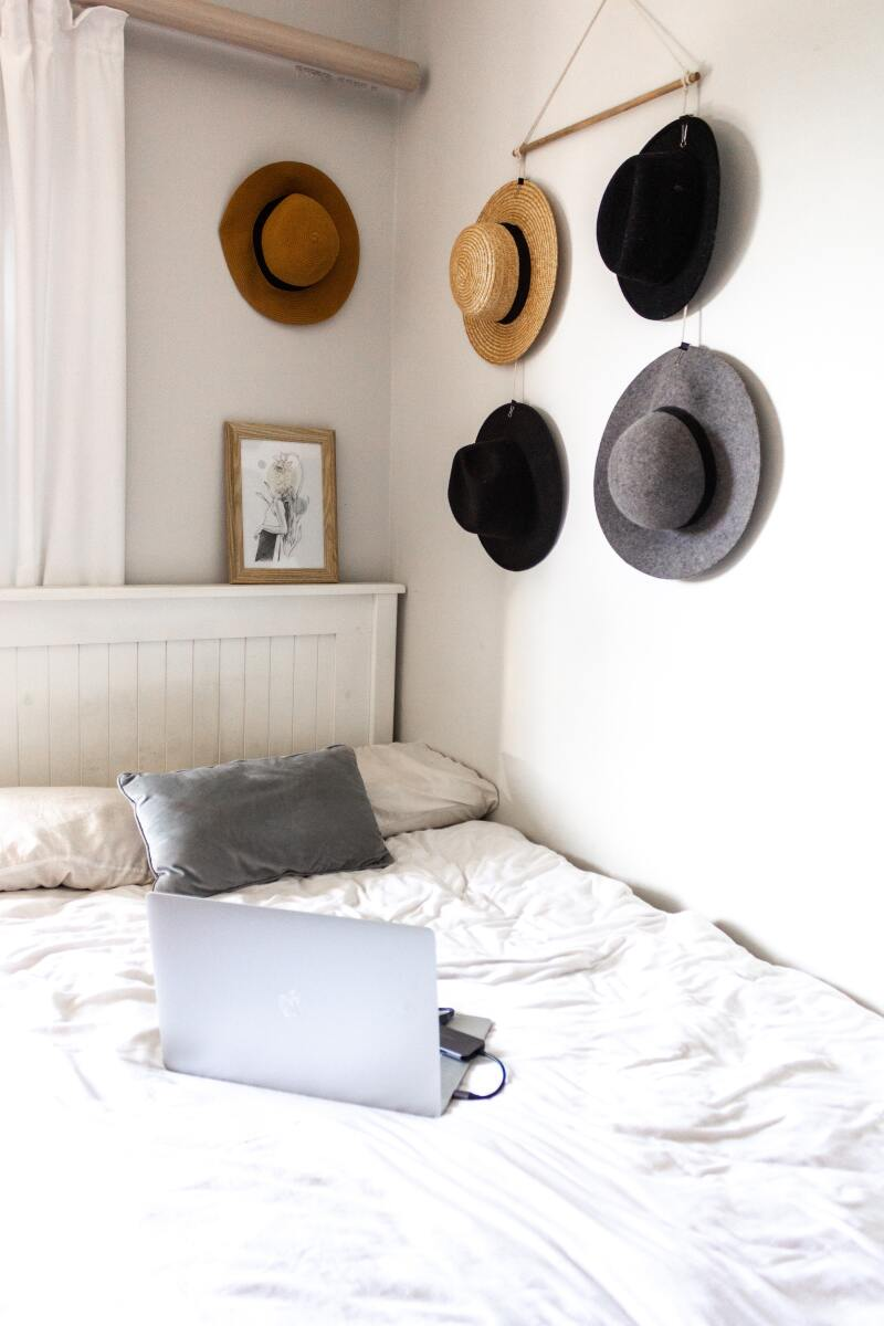 Hats hanging on a wall as decoration in a bedroom