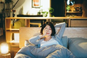 Woman waking up very tired, rubbing her eyes from lack of sleep