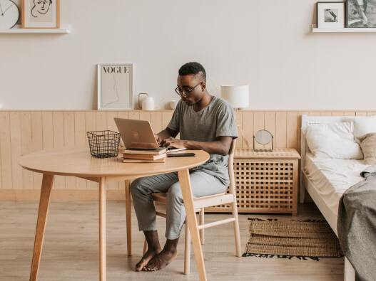 Man working on a laptop at his desk near his bed