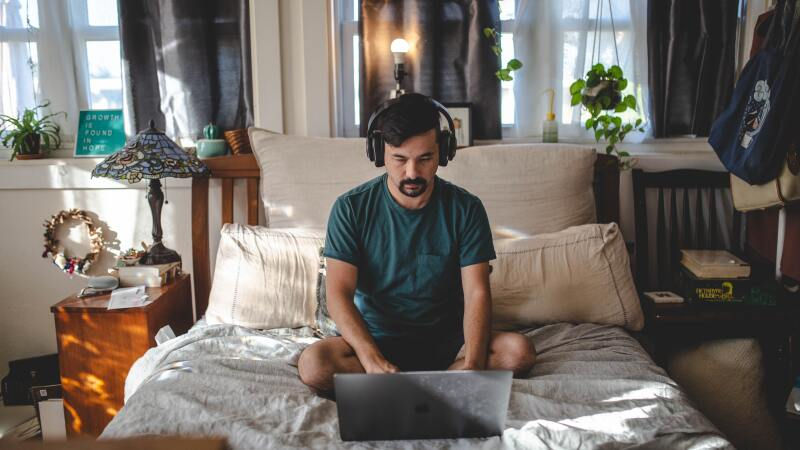 Man in green shirt listening to audio through headphones while sitting on his bed