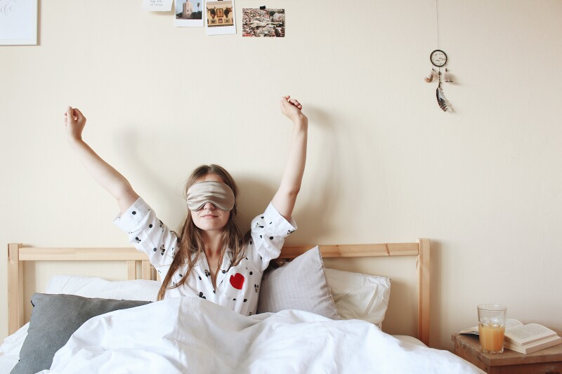 Woman wearing an eyemask, stretching in bed as she wakes up.