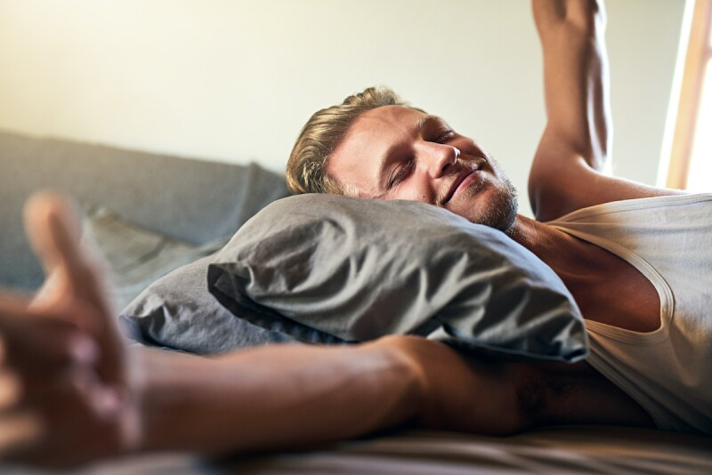 Cropped shot of a young man stretching while waking up in bed