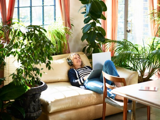 Older Woman sitting on couch, listening to mother's day music