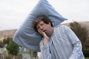 Man with a pillow in Mattress Firm Junk Sleep commercial