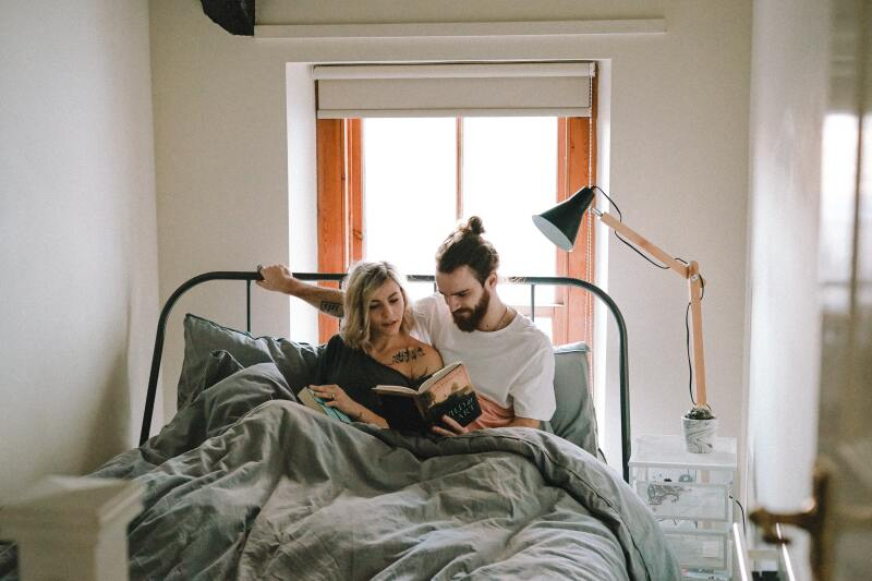 Man and a woman reading in bed