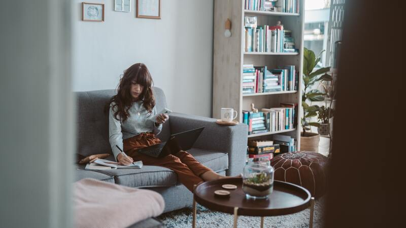Woman creating a to do list in her living room