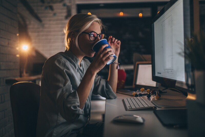 Woman drinking coffee at her computer late at night