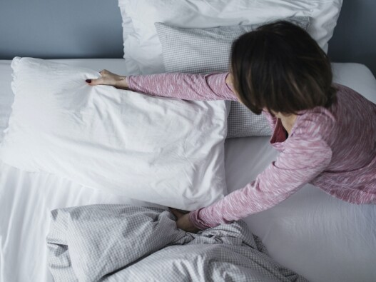 Person adjusting pillows on their bed before sleep