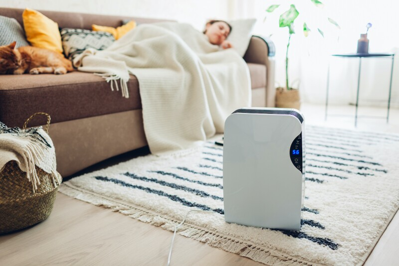 Woman napping on couch with an AC unit in a hot sleep