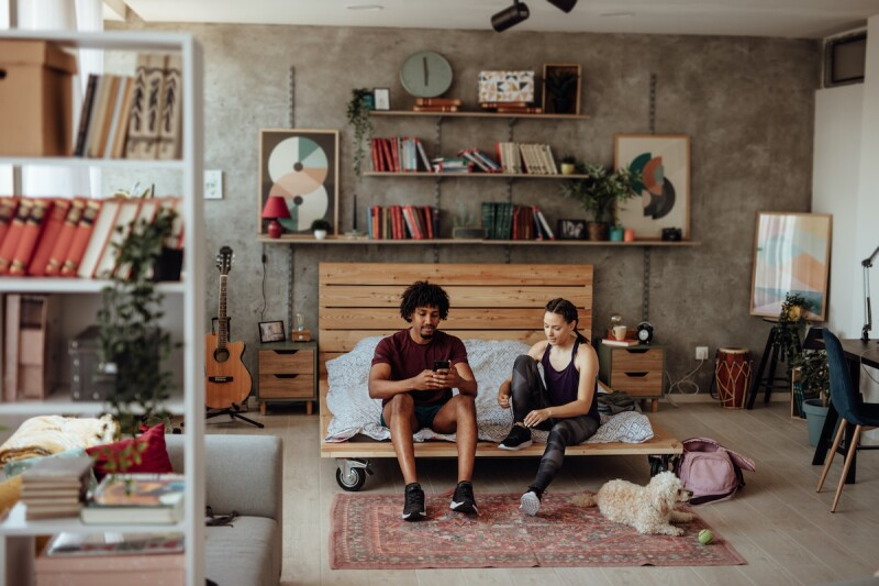 Two people sitting on a bed in a studio space that's been maximized with functional furniture and storage units