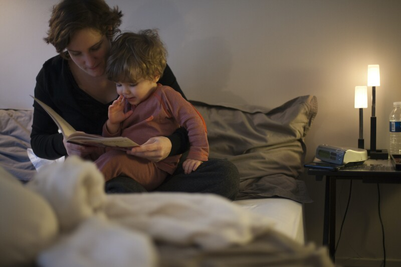 Parent reading a book to a child as part of their bedtime routine