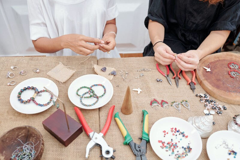 Two people using beads and string to make bracelets as a slumber party activity