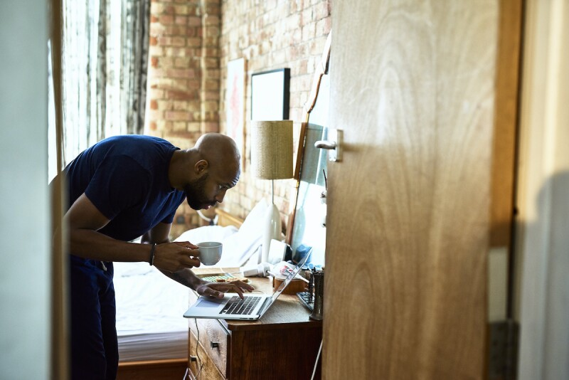 Man looking at his laptop in the morning with a cup of coffee, trying to get a quick start to his day