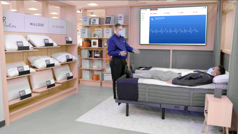 Mattress Firm Sleep Expert talking to a customer in a redesigned store with sleep tracking on a TV screen.