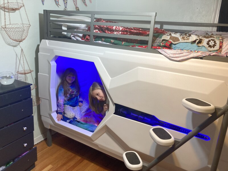 Two girls peeking out from their zPod bunk bed