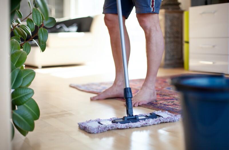 Man wipes down hardwood floor to reduce dust allergies in home