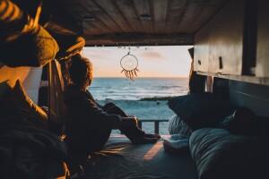 Woman sitting in camper van bed by beach.