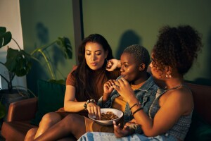 Three adults sharing a bowl of snacks while watching a movie at a sleepover