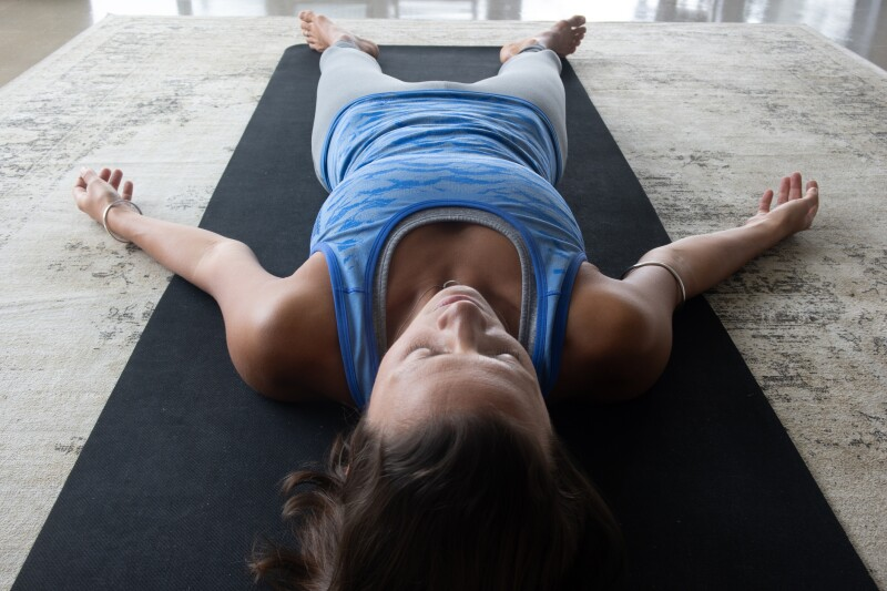 Person lying on yoga mat with arms stretched out for progressive muscle relaxation