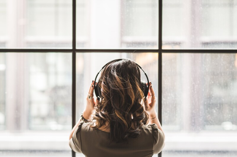 Woman with misophonia wearing headphones in front of a window.