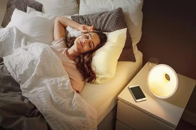 Woman waking up using a sunrise alarm clock