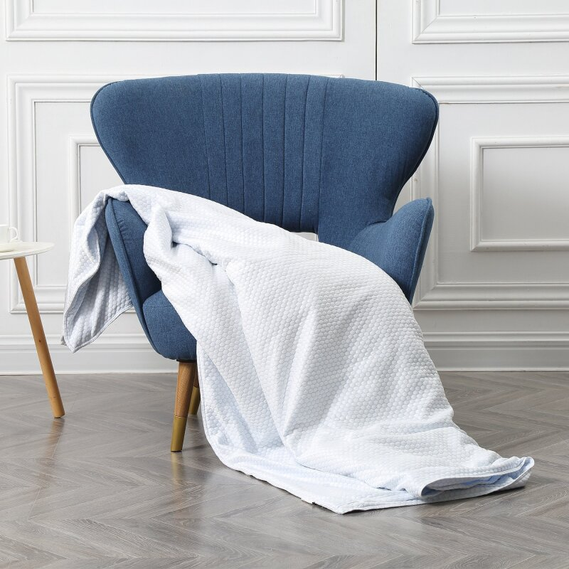 BlanQuil Chil weighted blanket draped on a blue chair.