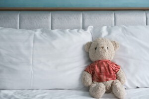Stuffed animal for an adult sitting against pillows on a bed.