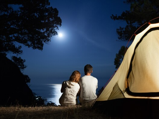 couple camping and looking at the moon over the ocean