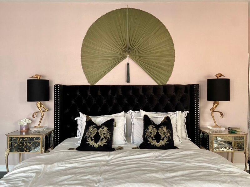 Glam bed and wall decor in a Hollywood Regency inspired bedroom.