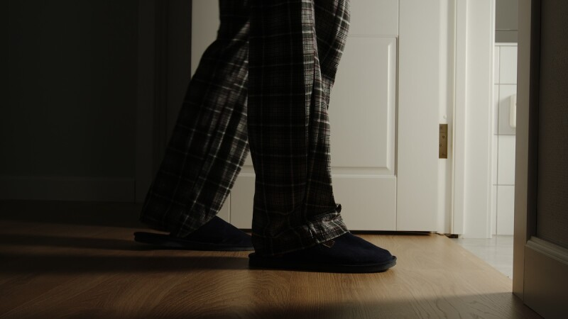 Man in pajamas with slippers walking to the bathroom for a late night pee