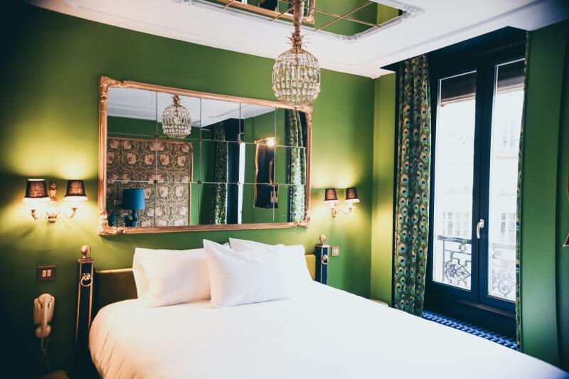 A chandelier hanging over a bed in a green bedroom