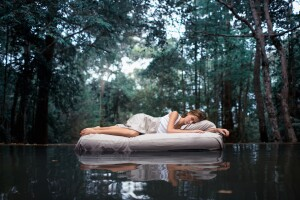 Woman dreaming on a mattress in the water