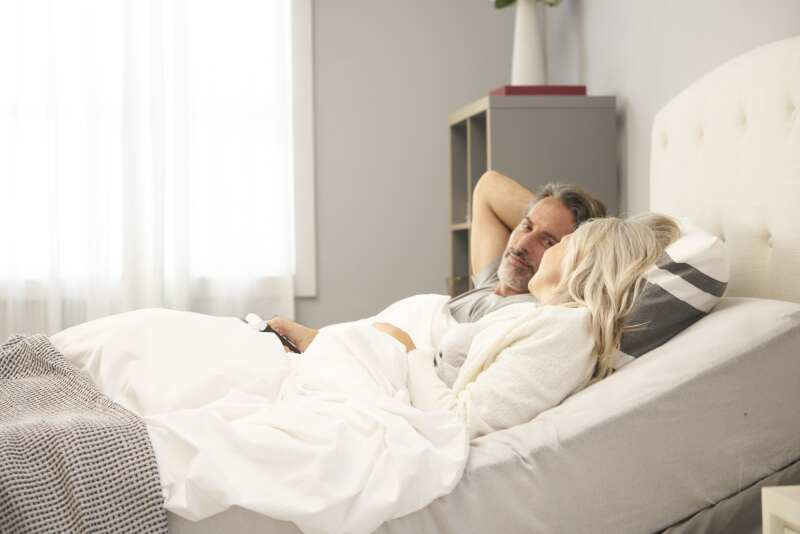 Man and woman in an adjustable bed with a remote