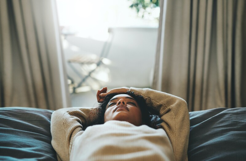 Woman closing eyes and relaxing on bed