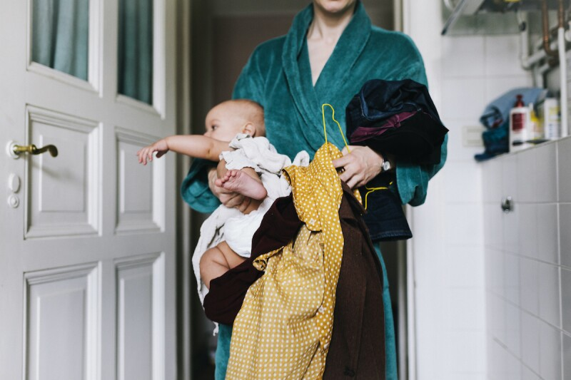 Mom wearing a bathrobe while carrying a baby, laundry, and extra clothes.