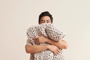 man hugging a bearaby weighted blanket.